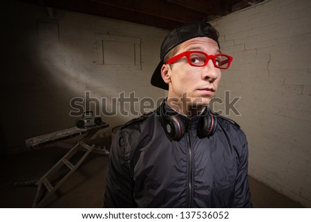 Conceited young man with red eyeglasses and earphones - stock photo