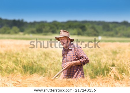 Conceived old man farmer resting in barley field after hard work - stock photo