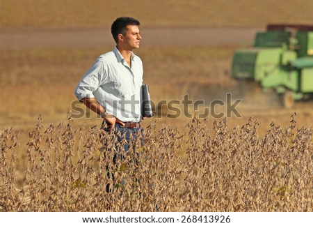 Conceived young businessman standing on soybean field during harvest - stock photo