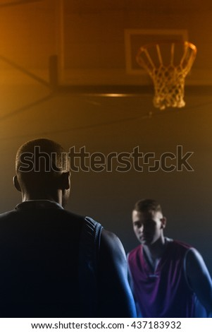 Concentrate basketball players playing in a gymnasium against a black background - stock photo