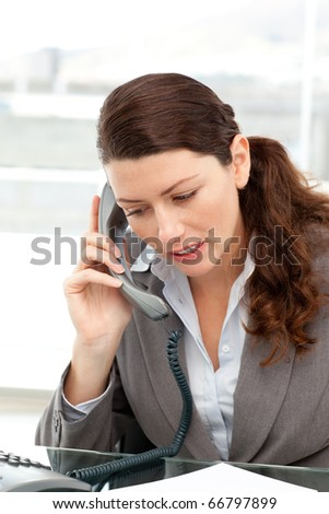 Concentrate businesswoman talking on the phone in an office