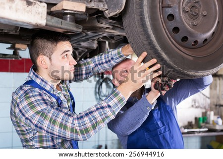 Concentrated adult mechanics repairing car of client