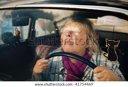 Concentrated and stressed senior woman driving an oldtimer car - stock photo