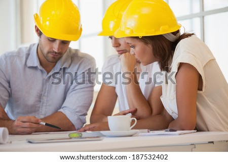 Concentrated architects in yellow helmets working on blueprints at the office - stock photo