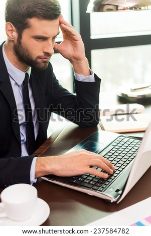 Concentrated at work. Concentrated young man in suit touching head with hand and looking at laptop while sitting at his working place - stock photo