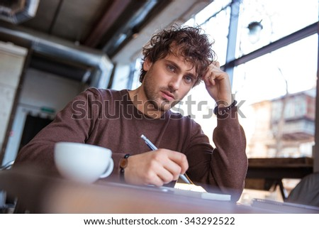 Concentrated attractive thoughtful curly pensive young male in brown sweetshirt sitting and writing in cafe - stock photo