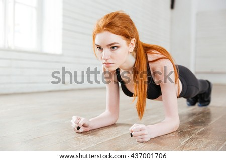 Concentrated beautiful fitness girl in sportwear exercising doing a plank in the gym - stock photo