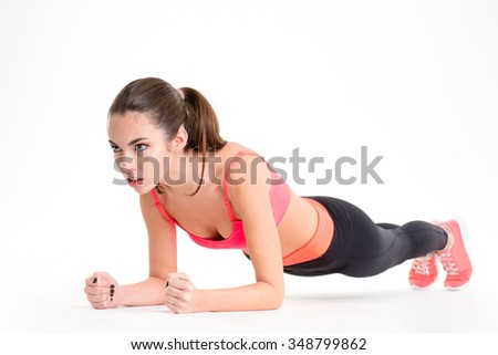 Concentrated beautiful fitness girl in sportwear exercising doing a plank over white background - stock photo