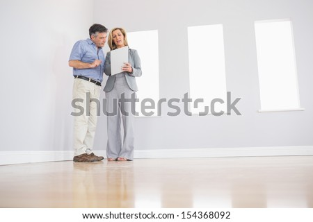 Concentrated blonde realtor showing an empty room and some documents to a potential attentive mature buyer - stock photo