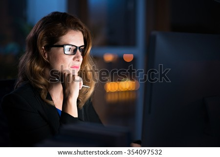 Concentrated business lady reading information on glowing screen on her computer - stock photo
