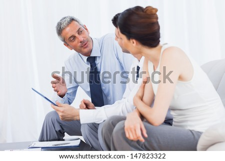 Concentrated business people talking about files on sofa at office