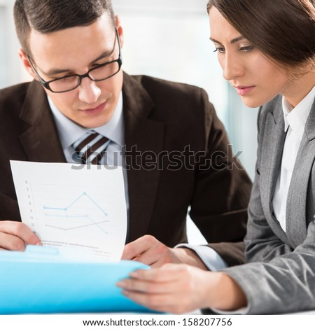 Concentrated business people with paper work at office - stock photo