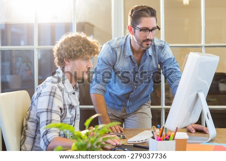 Concentrated business team working on computer in the office - stock photo
