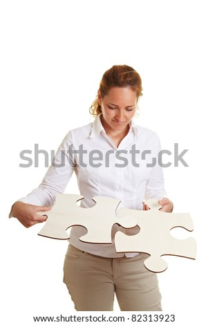 Concentrated business woman solving oversized jigsaw puzzle - stock photo