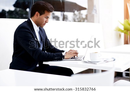 Concentrated businessman in elegant suit keyboarding text on his laptop computer while sitting on restaurant terrace at coffee break, successful freelancer working remotely on his portable net-book - stock photo