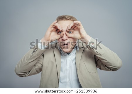 Concentrated businessman making binoculars with hands and looking through   - stock photo