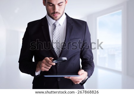 Concentrated businessman using magnifying glass against bright white corridor with windows - stock photo