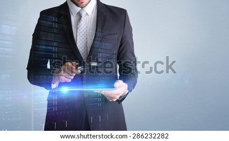 Concentrated businessman using magnifying glass against grey vignette - stock photo