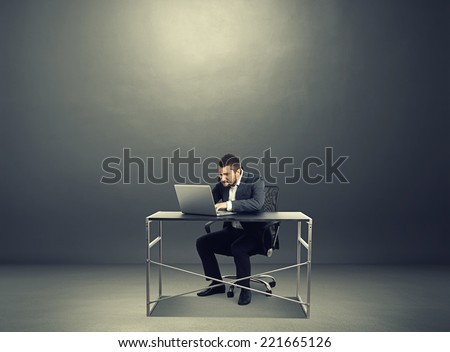 concentrated businessman working with laptop in the dark room with empty copyspace - stock photo