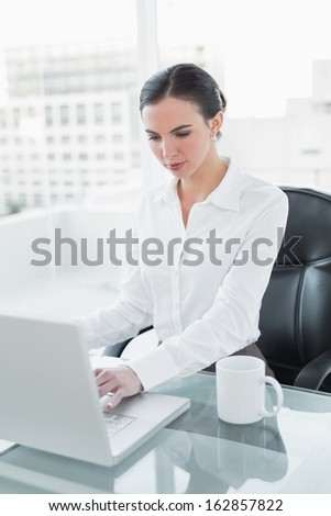 Concentrated businesswoman using laptop at desk in a bright office