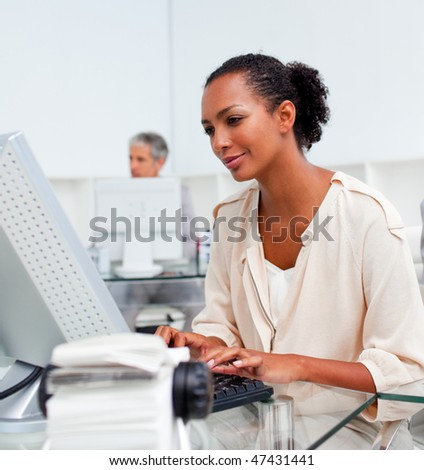 Concentrated businesswoman working at a computer in the office - stock photo