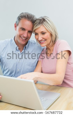 Concentrated content casual couple using laptop at home