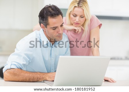 Concentrated couple using laptop in the kitchen at home