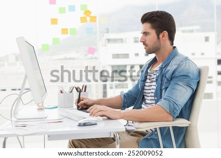 Concentrated designer using computer and digitizer in the office - stock photo