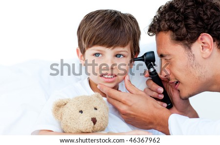 Concentrated doctor examining patient's ears at the hospital - stock photo