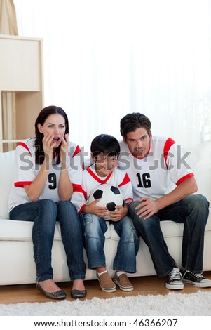 Concentrated family watching football match on television - stock photo