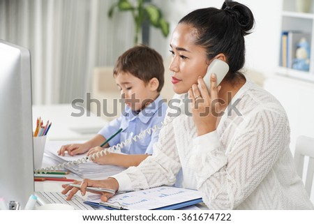 Concentrated female entrepreneur calling on the phone when her son drawing on documents