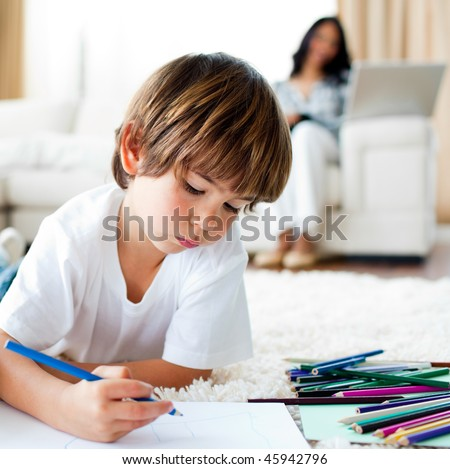 Concentrated little boy drawing and his sister eating chips in the living-room - stock photo