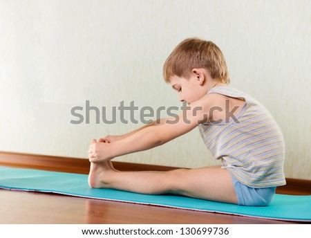 Concentrated little boy exercising and stretching in gym - stock photo