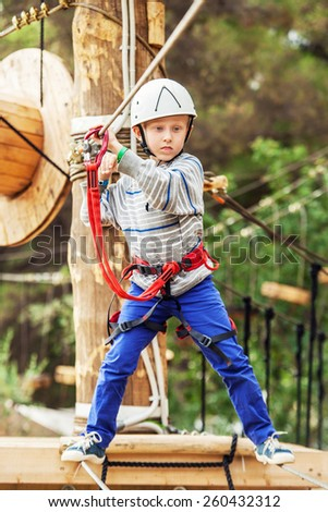 Concentrated little Boy on the rope track - stock photo