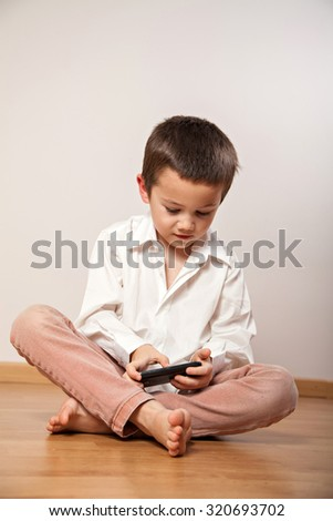 Concentrated little boy playing with mobile phone, smartphone - stock photo