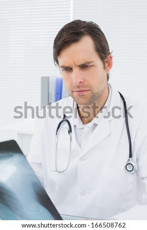 Concentrated male doctor looking at x-ray picture of lungs in the medical office