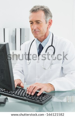 Concentrated male doctor using computer at the medical office - stock photo
