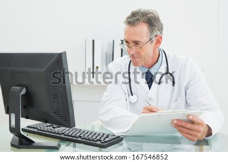 Concentrated male doctor with report looking at computer monitor at desk in medical office - stock photo