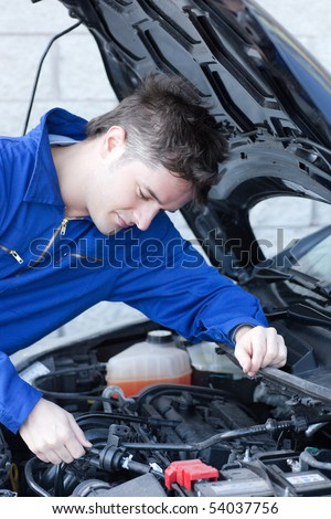 Concentrated  man repairing a car in a garage