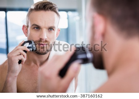 Concentrated man shaving his beard in bathroom