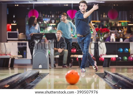 Concentrated man throwing ball in bowling club - stock photo