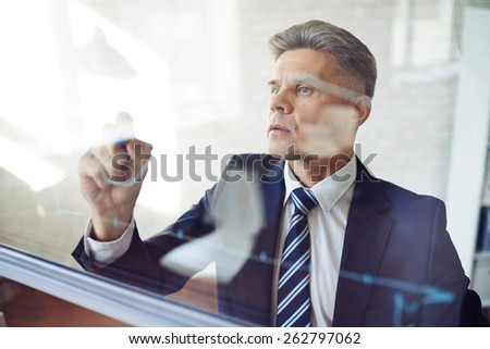 Concentrated man writing graph - stock photo