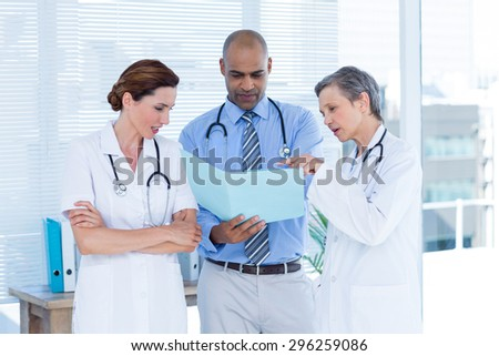 Concentrated medical colleagues analyzing file together in the hospital - stock photo