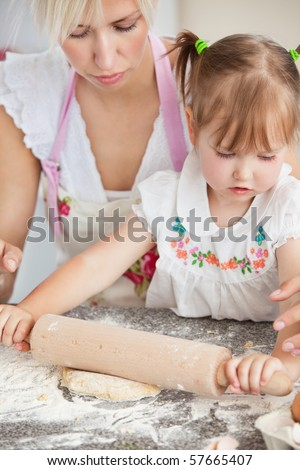 Concentrated mother and child baking cookies in kitchen - stock photo