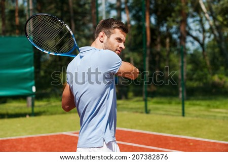 Concentrated on game. Handsome young man in polo shirt holding tennis racket and looking concentrated while standing on tennis court  - stock photo