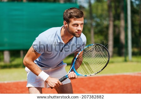 Concentrated on game. Handsome young man in polo shirt holding tennis racket and looking concentrated while standing on tennis court