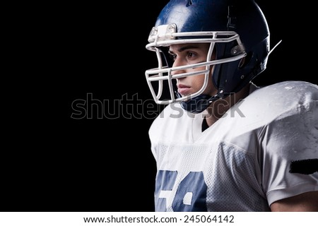 Concentrated on game.  Side view of American football player looking away while standing against black background  - stock photo