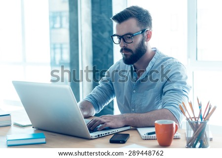 Concentrated on work. Concentrated young beard man working on laptop while sitting at his working place in office - stock photo