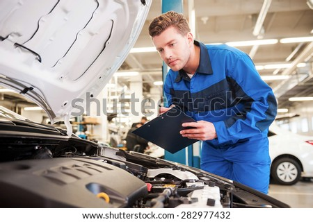 Concentrated on work. Concentrated young man in uniform examining car and writing something in clipboard while standing in workshop