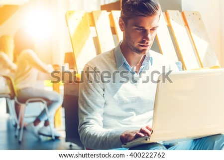 Concentrated on work. Concentrated young man working on laptop while his colleagues working in the background  - stock photo